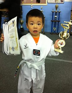 Tommy Geng at age five, receives his senior white belt. Photo credit: Dondi Tondro-Smith.