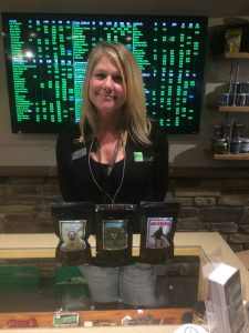 """Karry Johnson shows off some of her favorite products. She wants to help erase the stigma people have about marijuana users. """"We're not lazy,"""" she said. Photo credit: Sara Holodnick."""