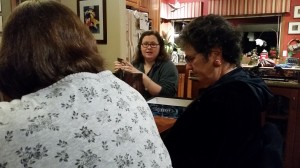 """At an informal game gathering, Beth (center) sets up the game """"Mysterium"""" and instructs players, including Colleen Verdon (L) and Molly Monahan (R), on game set up, play, rules and strategy. Photo courtesy: Beth Sobel."""
