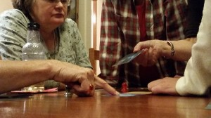 """Collen Verdon points out to the other """"Mysterium"""" players her reasoning for determining the killer and the murder method used. Photo courtesy: Beth Sobel."""