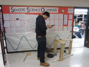 Senior Nick Coats stands before the organizational bulletin board as he works on the final touches of an air trajectory machine he designed and built with the help of teammates.