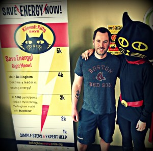 """Bellingham resident, Derek, is being congratulated by Kilowatt Kitty after being drawn as the first winner of """"Free Utilities for a Month"""" for connecting his utilities in the Energy Center at BellighamEnergyPrize.org. Photo courtesy: Sustainable Connections."""