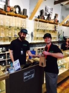 Owner Quinn Sharp made the first ceremonial purchase at Satori from General Manager, Joshua Besecker. Photo courtesy: Satori Cannabis Boutique.