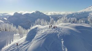 Skiers stand and celebrate atop the snowy mountains as Redal's drone soars overhead. Photo courtesy: Screenshot from Above Bellingham.